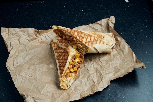 Rolo apetitoso de shawarma com carne, salada e molho caseiro em pão pita fino em papel ofício em uma mesa preta ... cozinha oriental. quibe fatiado com carne grelhada.