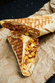 Rolo apetitoso de shawarma com carne, salada e molho caseiro em pão pita fino em papel ofício em uma superfície preta. cozinha oriental. quibe fatiado com carne grelhada.