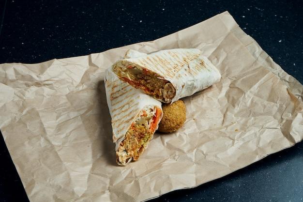 Rolo apetitoso de shawarma com falafel, salada e molho caseiro em pão pita fino em papel ofício em uma mesa preta ... cozinha oriental. quibe fatiado com falafel.