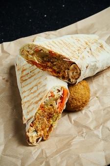 Rolo apetitoso de shawarma com falafel, salada e molho caseiro em pão pita fino em papel ofício em uma superfície preta. cozinha oriental. quibe fatiado com falafel.
