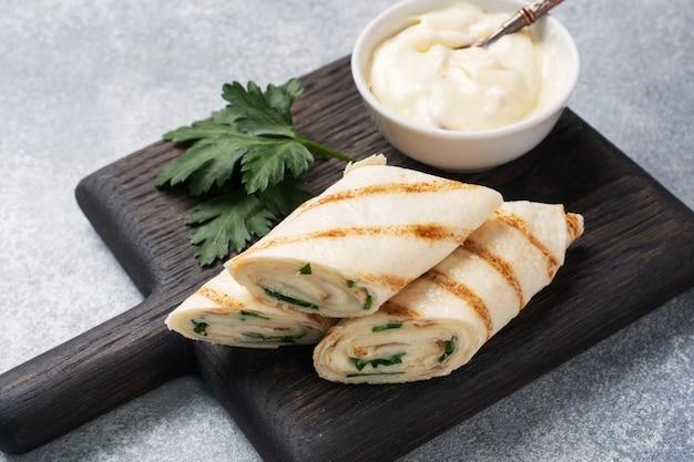 Rolo com queijo e ervas. pão pita grelhado com recheio. salada de rabanete de pepino. conceito de um pequeno-almoço saudável.