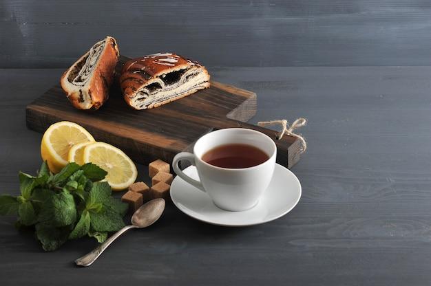 Rolo com sementes de papoila, chá, limão e hortelã na superfície de madeira