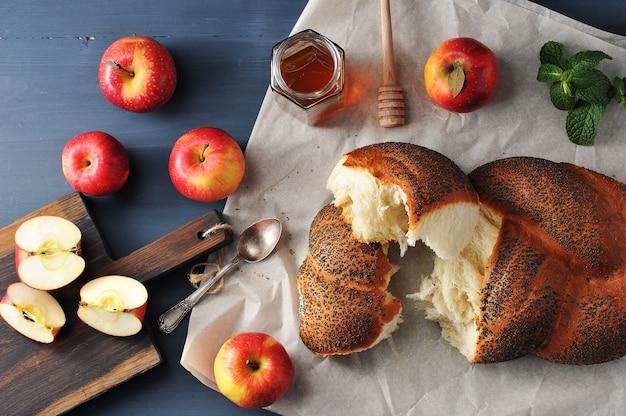 Rolo com sementes de papoila, rasgadas em pedaços closeup tiro com maçãs e mel