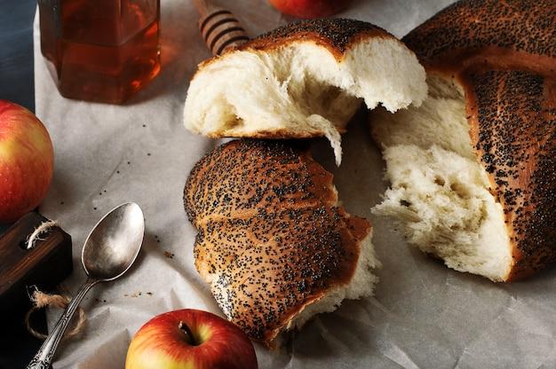 Rolo com sementes de papoila, rasgadas em pedaços closeup tiro - maçãs e mel