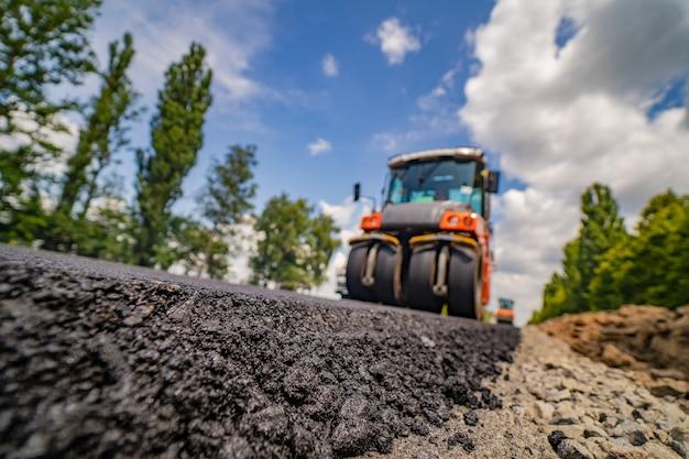 Rolo compactador aplainando asfalto novo