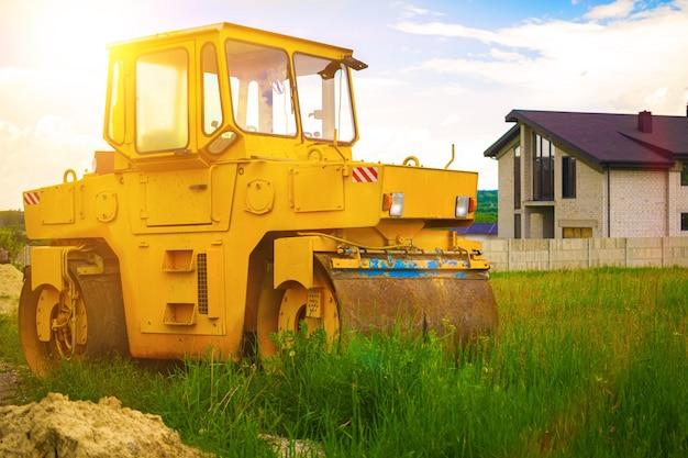 Rolo compactador no campo ao pôr do sol, maquinaria pesada para a área de construção e desenvolvimento de terras, foto de fundo do sol