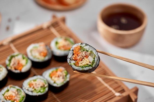Rolo coreano gimbap (kimbob) feito de arroz branco cozido no vapor (bap) e vários outros ingredientes