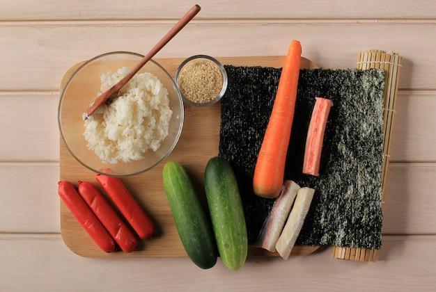 Rolo coreano gimbap (kimbob ou kimbap) preparação de ingredientes. arroz, salsicha, palito de caranguejo, laver, alga marinha, pepino, cenoura e semente de gergelim