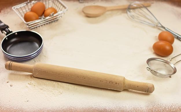 Rolo da massa, batedor, peneira, frigideira pequena, ovos e farinha polvilhada em uma mesa de madeira