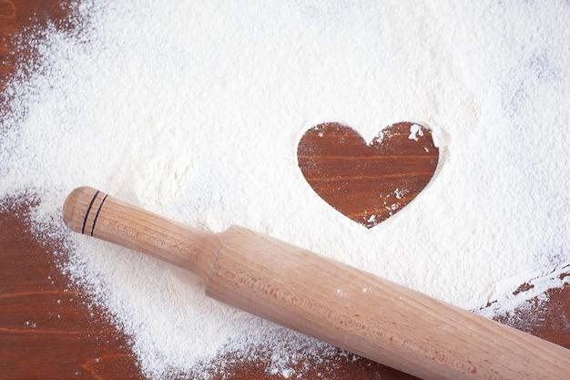 Rolo da massa e farinha polvilhada com o símbolo do coração na mesa de madeira