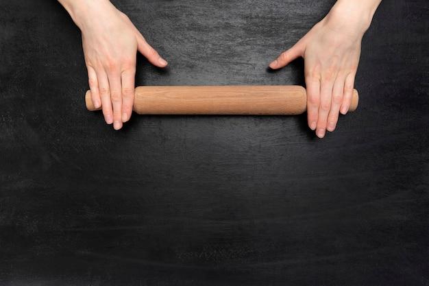 Rolo da massa nas mãos sobre fundo preto de madeira, vista superior. copie o espaço.
