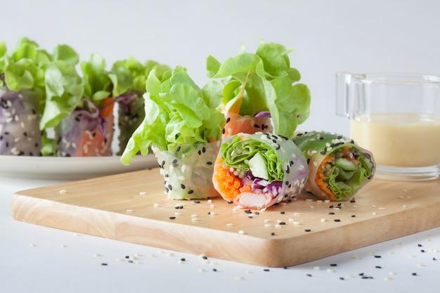 Rolo da salada caseiro na placa de madeira com molho de creme sobre para trás.