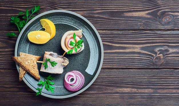 Rolo de arenque no espeto com salsa, cebola e rodela de limão, vista de cima. os sanduíches são dispostos em um prato, sobre uma mesa de madeira escura com espaço para texto. fast food ou lanche