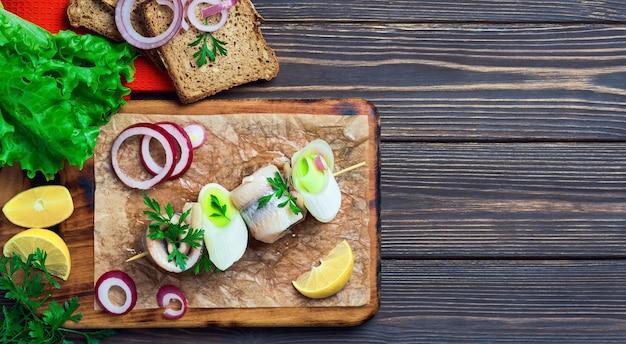 Rolo de arenque no espeto com salsa, cebola e rodela de limão, vista de cima. os sanduíches são dispostos sobre uma tábua de cortar, sobre um fundo escuro de madeira com espaço para texto. fast food ou lanche