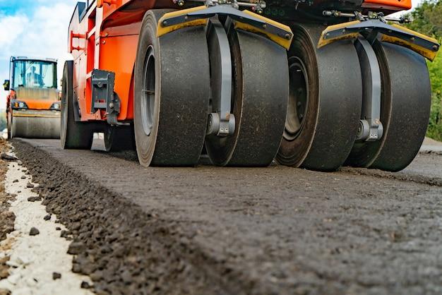Rolo de asfalto que empilha e pressiona o asfalto quente enquanto faz uma nova estrada.