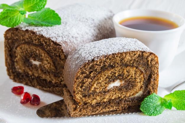 Rolo de biscoito de chocolate e uma xícara de chá na mesa de madeira branca.