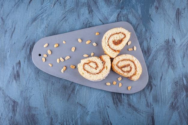 Rolo de biscoito fatiado com recheio de chocolate colocado sobre uma placa cinza.