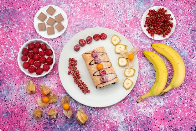 Rolo de bolo dentro do prato com chá de banana e morangos na mesa colorida bolo biscoito doce de frutas