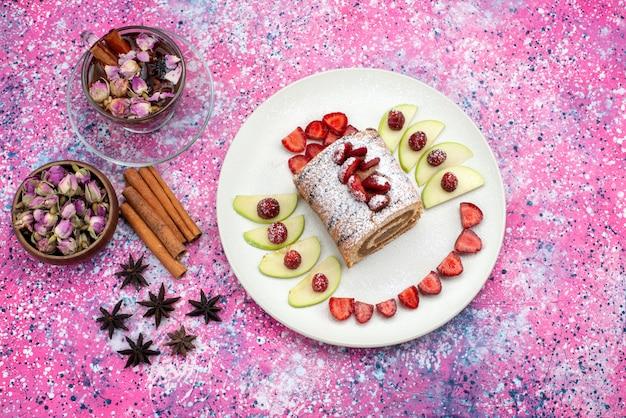 Rolo de bolo dentro do prato com maçãs e morangos junto com canela e chá na mesa colorida.