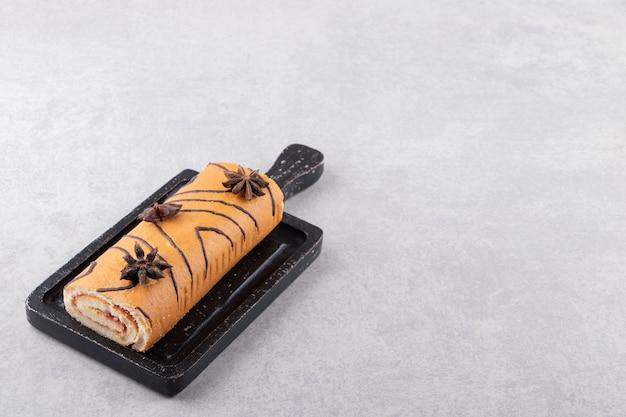 Rolo de bolo fresco na placa de madeira sobre fundo cinza.