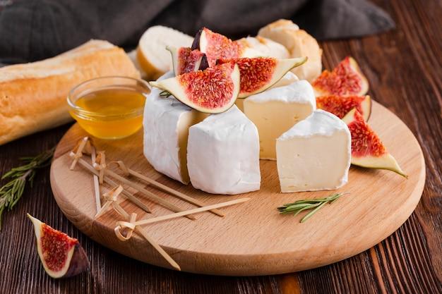 Rolo de camembert fatiado de alto ângulo com figo
