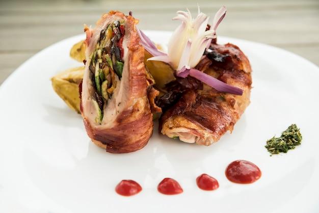 Rolo de carne assada com molho no prato branco