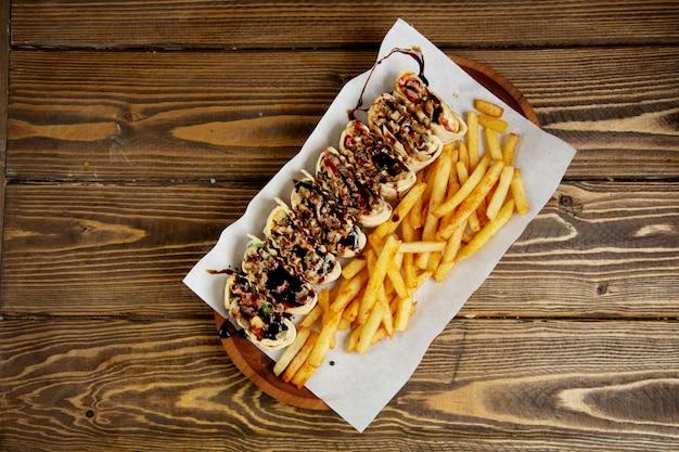 Rolo de carne fatiada em pão pita e batatas fritas vista superior