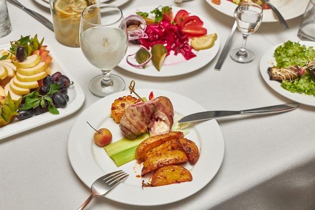 Rolo de carne recheado com queijo com batatas fritas e milho como prato principal em um restaurante