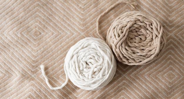 Rolo de corda de macramê. fio branco e cinza em um lindo fundo pastel