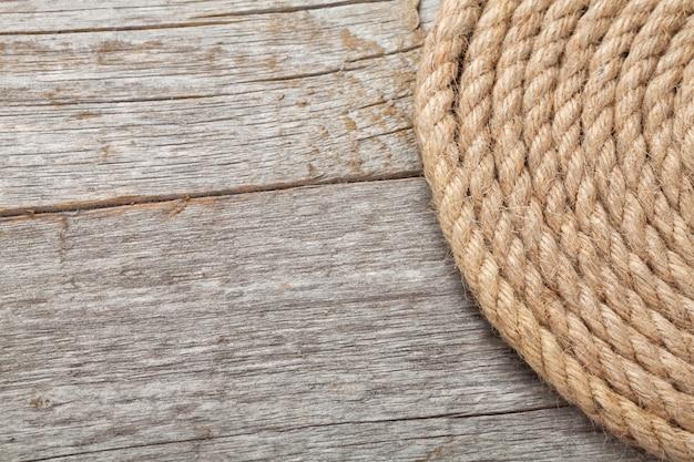 Rolo de corda de navio em fundo de textura de madeira