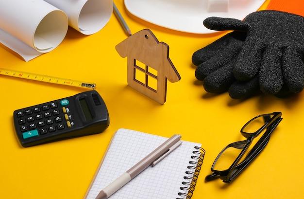 Rolo de desenhos, ferramentas de engenharia e artigos de papelaria em fundo amarelo, conceito de construção de casa