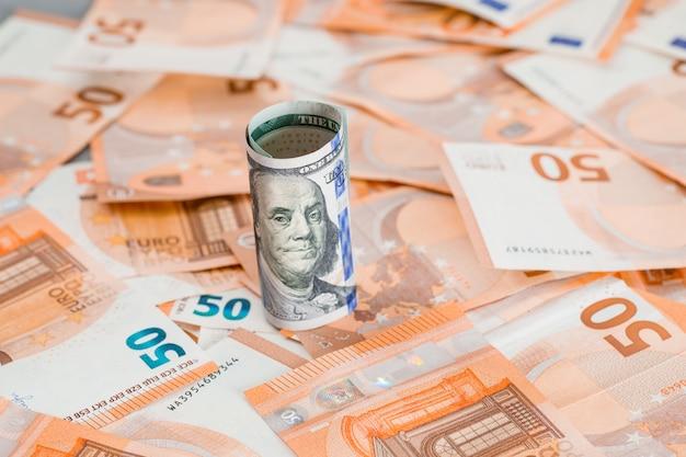Rolo de dinheiro na mesa cinza e notas.