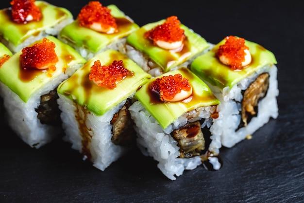 Rolo de dragão verde de vista lateral com molho de soja de abacate de peixe frito e caviar tobiko por cima