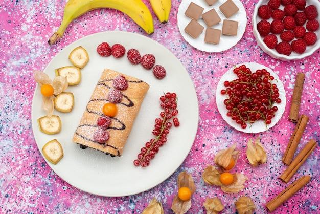 Rolo de fatias de bolo com diferentes frutas dentro de um prato branco sobre o fundo colorido do biscoito doce