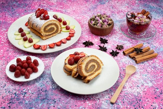 Rolo de fatias de bolo com diferentes frutas dentro do prato com chá na cor doce do biscoito de fundo colorido