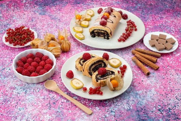 Rolo de fatias de bolo com frutas diferentes dentro de um prato branco na cor doce do bolo de fundo colorido