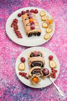 Rolo de fatias de bolo com frutas diferentes dentro de um prato branco no fundo colorido bolo de biscoito doce