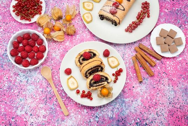 Rolo de fatias de bolo com frutas diferentes dentro de um prato branco no fundo colorido bolo de bolacha de cor doce