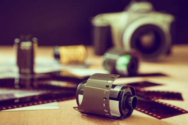 Rolo de filme fotográfico de 35 mm com câmera velha na mesa de madeira. tom vintage