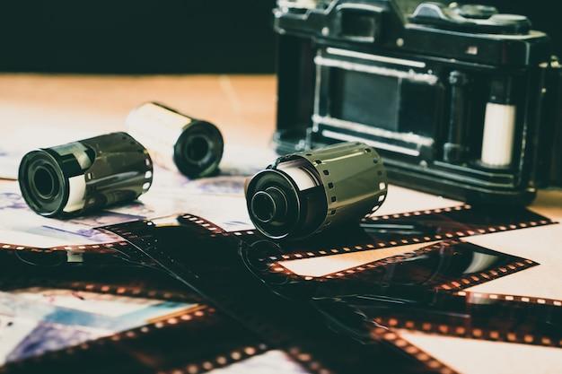 Rolo de filme fotográfico de 35 mm com câmera velha na mesa de madeira.