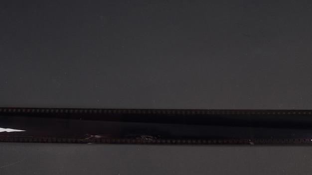 Rolo de filme fotográfico de câmera 35mm isolado em fundo preto.