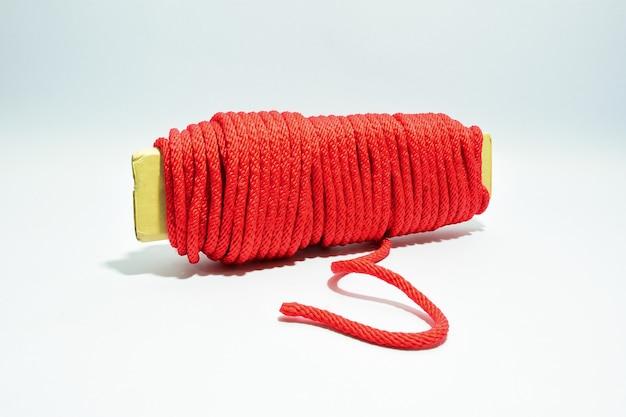 Rolo de fio de corda vermelha único sobre um fundo branco