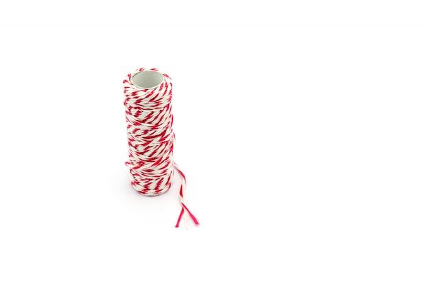 Rolo de fio vermelho e branco isolado no fundo branco