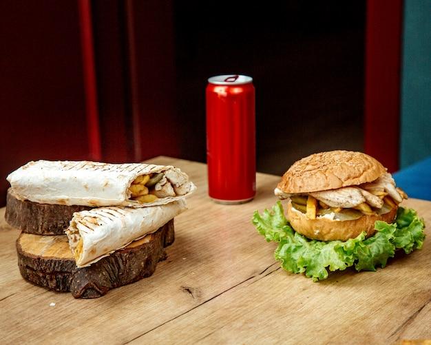 Rolo de frango em pão pita e hambúrguer de frango em cima da mesa