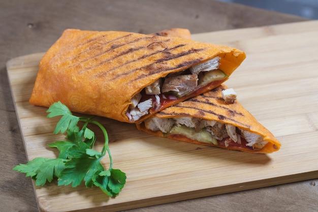Rolo de frango shawarma em um pão árabe em fundo de madeira.