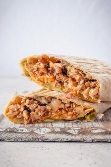 Rolo de frango shawarma em uma pita com legumes frescos e molho de creme