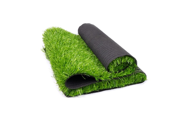 Rolo de grama verde artificial, isolado no fundo branco, cobrindo playgrounds e recintos desportivos.