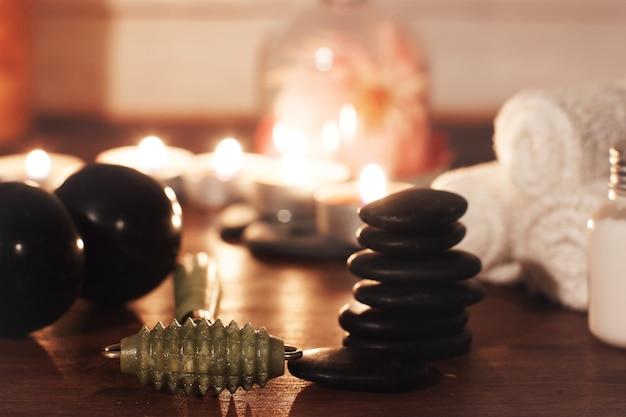 Rolo de jade verde para massagem facial em mesa com acessórios de spa