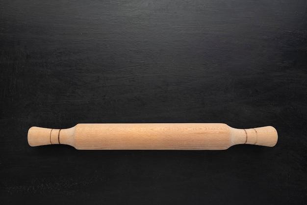 Rolo de madeira em fundo preto, vista superior. copie o espaço, o conceito de cozinha.