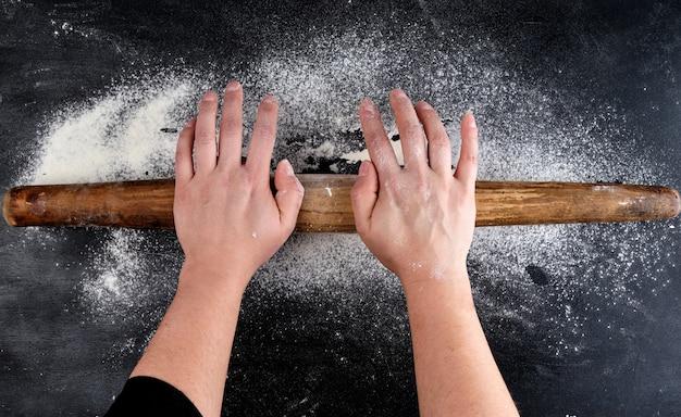 Rolo de madeira marrom nas mãos femininas em preto com farinha de trigo branca